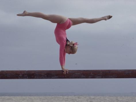 Gymnast Cathy Rigby performing split leg handstand on balance beam.