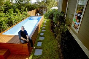 Stefan Beese sits next to the backyard swimming pool he made from a 22-foot-long steel refuse container.