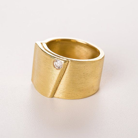 Wide wedding ring made of 18K gold with matte brushed texture, set with high qaulity diamond 0.15 (4mm). The ring surface is made of double layers to emphasize the ring attendance. If you are looking for a different look, this is the ring that would express how unique you are.