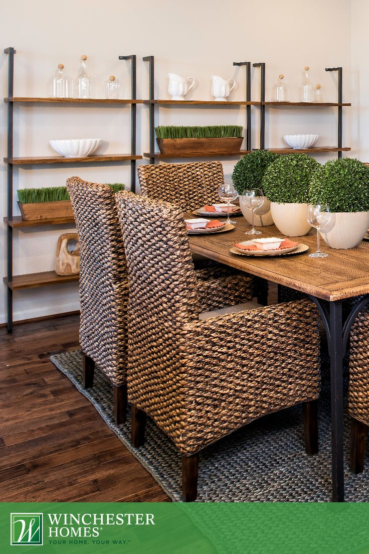 Wicker Dining Chairs, Set Atop A Dark Jute Rug, Are Tastefully Paired With A