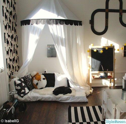 Rincón de lectura en blanco y negro, con dosel, muchos cojines y un pequeño colchón...