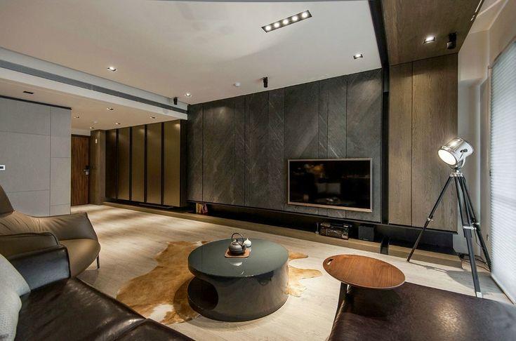 Phòng khách là khu vực trung tâm của căn hộ, với sự kết hợp của các đường ngang trong lối décor tối giản tạo nên vẻ ấm cúng mà không kém phần sang trọng. Màu sắc của vật liệu và vật dụng nội thất kết hợp chiếu ánh sáng rất tinh tế tạo nên một không gian thư giãn tươm tất và tao nhã. Sự tương phản mạnh giữa cái rắn rỏi, thô mộc của Đá và Gỗ ở các vách trang trí, sàn nhà với bộ sofa bọc da mềm cùng đường nét, kiểu dáng đơn giản tạo nên sự thanh lịch & nam tính cho không gian