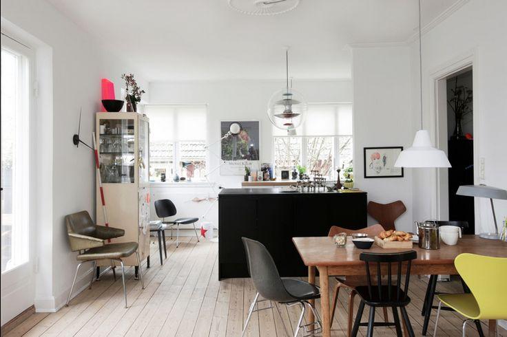 Mysigt kök med apotekarskåp och udda stolar.