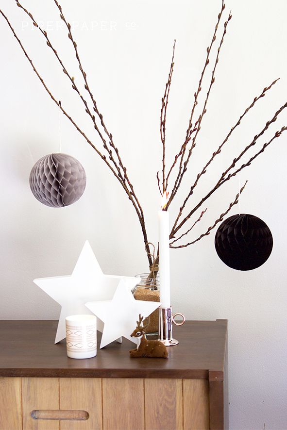 These Christmas mantle decorations have a real scandinavian style going on with it's bare branches, copper, grey, black and white colour palette. Love the combination of honeycomb balls, reindeer, stars and candles. Tapered candles give a real sophisticated style to the whole look.