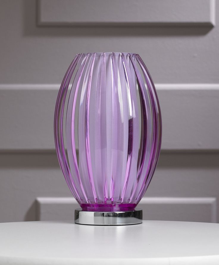 The Gemma is a modern table lamp; a semi-transparent shade with a curved, fluted finish sits on a circular chrome coloured base.