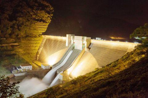 巨大な月山ダムの堤体と自然放流のライトアップ=昨年5月