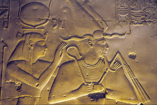 Goddess Isis embraces her seated husband, Osiris, Temple of Seti I, Abydos.