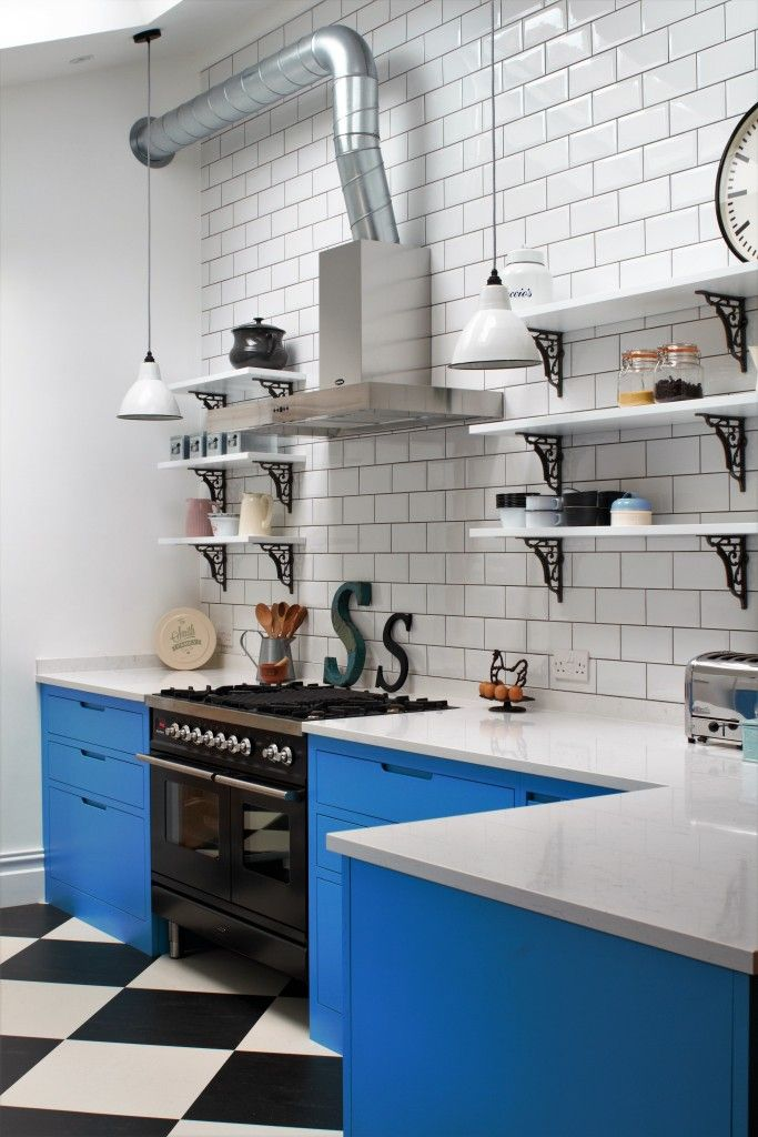 Sustainable Kitchens - Industrial Kitchen with American Diner Feel. A black Ilve Roma Twin Range cooker set within St Giles Blue Farrow & Ball painted flat panel cabinets with routed pulls. Open shelving on vintage Duckett design brackets with metro tiles and dark grout go beautifully with the bianco venato worktop. The open ducting create a fresh industrial vibe. The checkered floor gives the kitchen a playful feel.