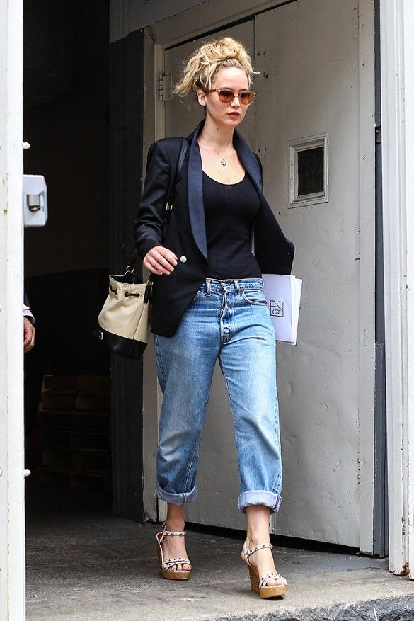 Jennifer Lawrence wears a black top, black structure blazer, wedges and a tan bucket bag.