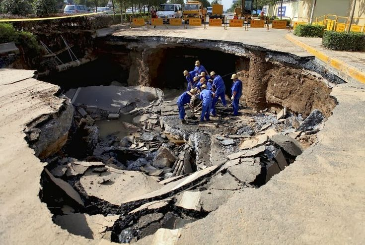 Workers repair a cave-in area on a road in Xi'an, Shaanxi province May 27, 2012.