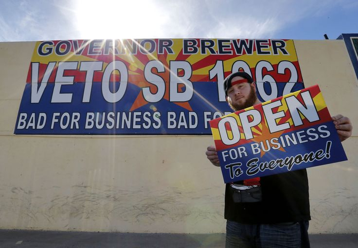 Josh Deinert, a graphic designer at Fast Signs in Phoenix, shows off a sign opposing the controversial Arizona bill SB 1062. Gov. Jan Brewer will hold a series of private meetings with opponents and proponents of legislation adding protections for people who assert their religious beliefs in refusing service to gays.