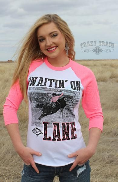 "We're lovin' this great shirt from Crazy Train!  Jump on board with our 'Waitin' on Lane' baseball tee in flashy pink.  Look ..don't wait to get this great baseball tee!  Graphic of Lane Frost 3/4 length Pink Raglan Sleeve 1"" Baby Rib Neckband White body with Pink, White and Black Rodeo/Bull Rider Graphics True Fit..runs true to size."