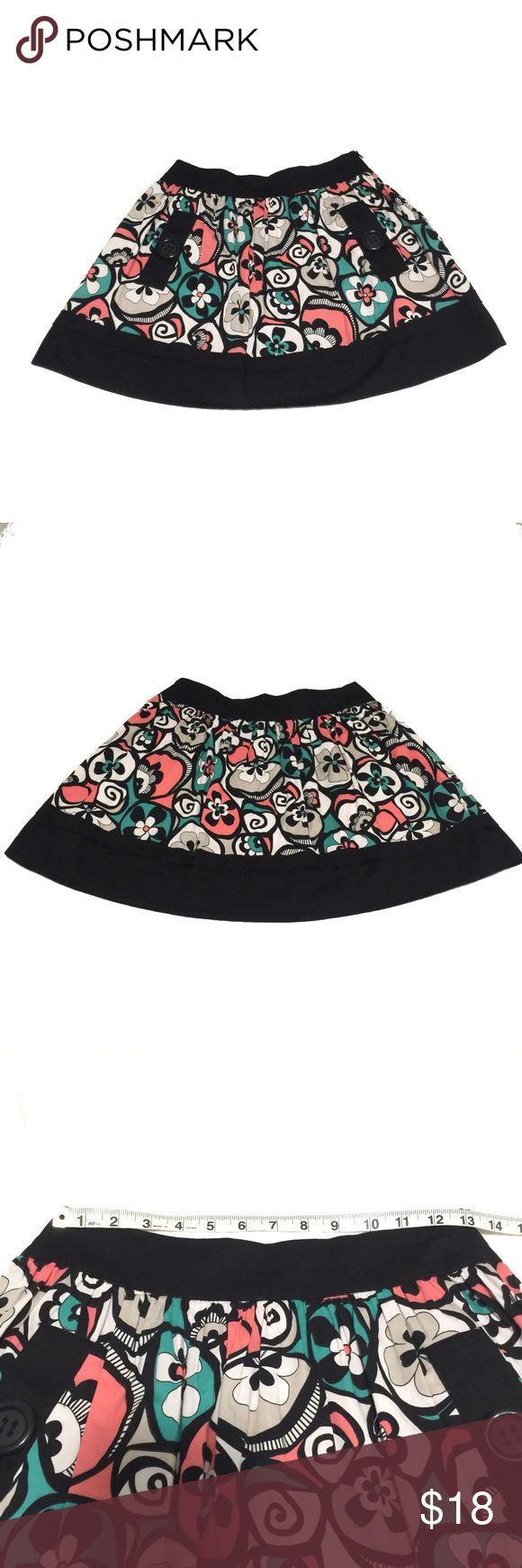 Candie's Tropical Floral Mini Skirt with Pockets This Candie's mini skirt has a cute tropical floral pattern with blooms that resemble Hibiscus flowers. The colors include a salmon pink shade, green, tan, and white. The skirt features a black waistband, a side zipper, two front pockets with button accents and a black ruffle trim. A cute piece to add to your wardrobe and perfect for spring (Spring Break!) and summer. Cotton spandex blend. Size 0. EUC. Gently used. Smoke-free, dog friendly…