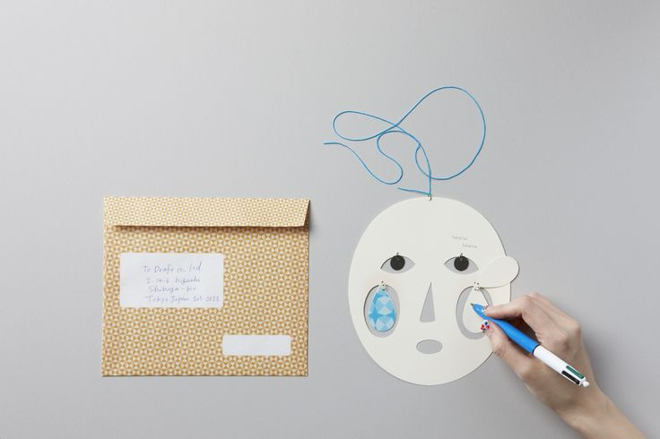 """「Buranco」 Greeting cards double as fanciful dangling mobiles. Available in smiling """"Merry"""" or somber """"Tears"""" versions, the cutout cards swing from colored strings, adding a touch of whimsy to any greeting.Cheek parts are backed with white paper, providing space to write a personal message."""