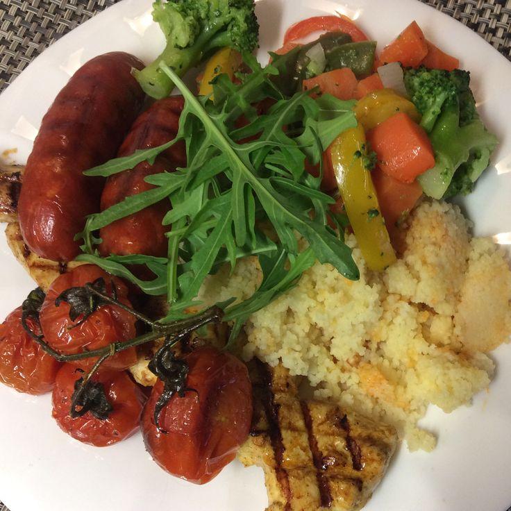 Ovengebakken trostomaatjes met chorizo worst en kipspiesje wat couscous gemengde groenten( broccoli, wortel, gele, rode en groene bellpepper) en als garnituur rucola.