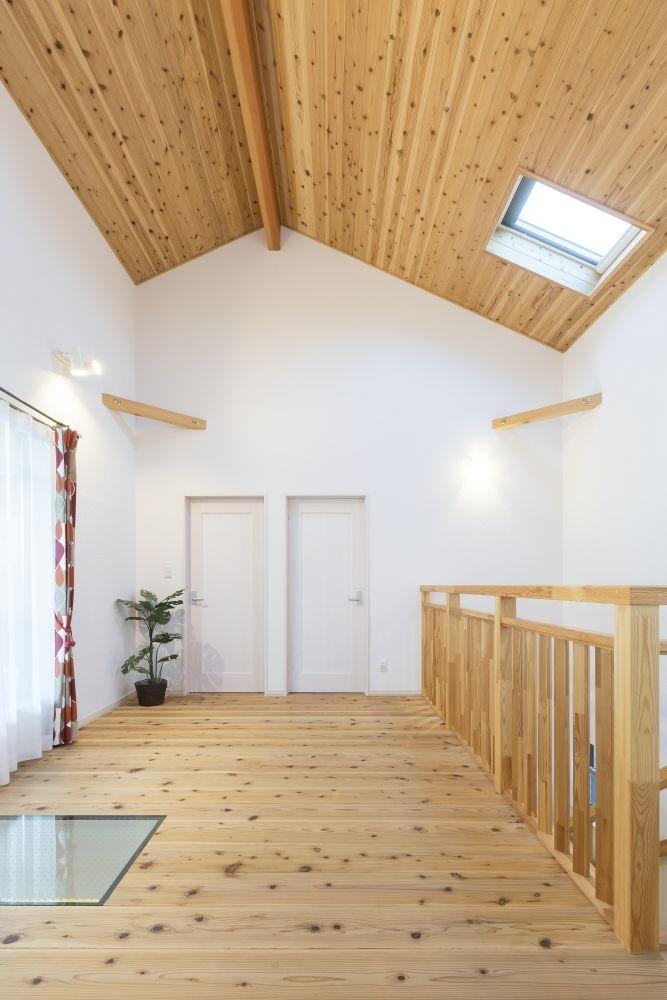 杉の無垢床フロアと造作階段手摺 杉羽目板の勾配天井と白い壁の