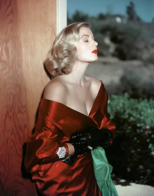 Anita Ekberg in an off-the- shoulder red satin dress...
