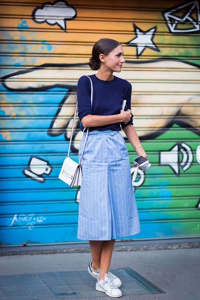 Diletta Bonaiuti wears navy blue top, blue pleated midi skirt and white Adidas sneakers.