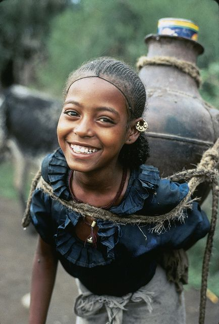Africa |  Beautiful smiling Ethiopian girl, as she carries a heavy load of water home |  © Peace Corps, via Flickr