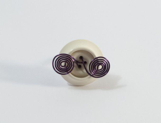 Anello realizzato a mano con filo di rame di colore viola e bottone bianco.