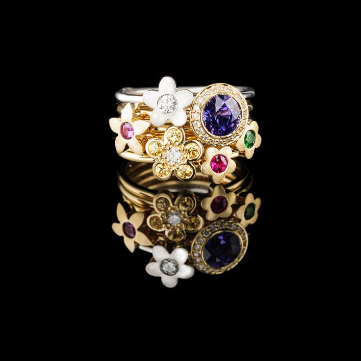 A stack of six of our Flower rings set with tsavorites, diamonds and sapphires. The large purple Sapphire is just spectacular.