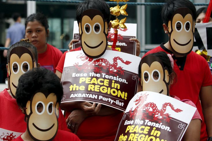 Activists from the Akbayan party-list group wear monkey masks during a protest outside the Chinese Consulate in Makati, Friday. The group trooped to the Chinese consular office to welcome the Lunar...