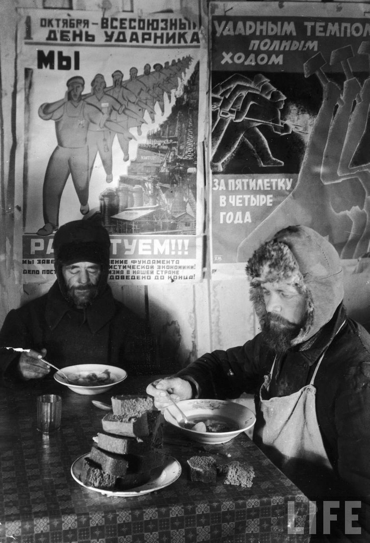 Two Russian workers eating black bread and soup at a table in front of a wall covered with propaganda posters, Magnitogorsk, 1931 by Margaret Bourke-White