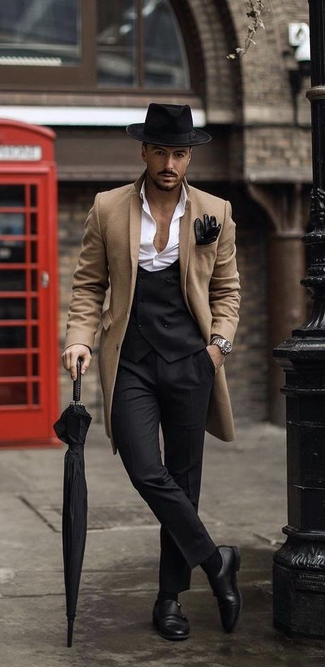 @rowanrow – with a fall business casual combo with a black fedora black leather gloves camel hair topcoat silver banded watch black deep cut waistcoat white button up shirt black umbrella black trousers black double monk shoes #waistcoat #menswear #gentlemen #classy #menstyle #mensfashion #fedora #umbrella #businesscasual #topcoat #dapper #gq #doublemonks