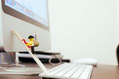Lego mini figure thief on apple computer. stock photo