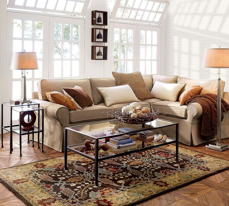 pottery barn living room with glass table and table lamp