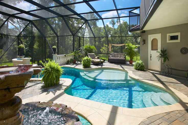 Curvy pool with fountain under screen enclosure ...