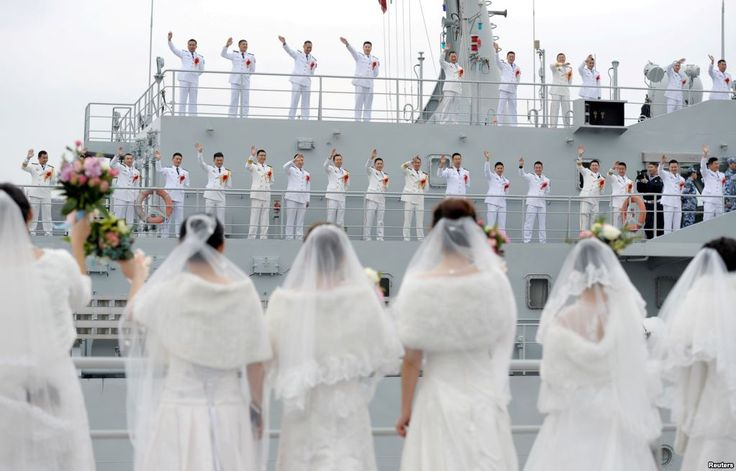 Navy personnel of People's Liberation Army (PLA) wave at their brides during a mass wedding at a military base in Zhoushan, Zhejiang province, China. (Reuters) https://pow.photos/2018/international-pow-26-december-1-january/