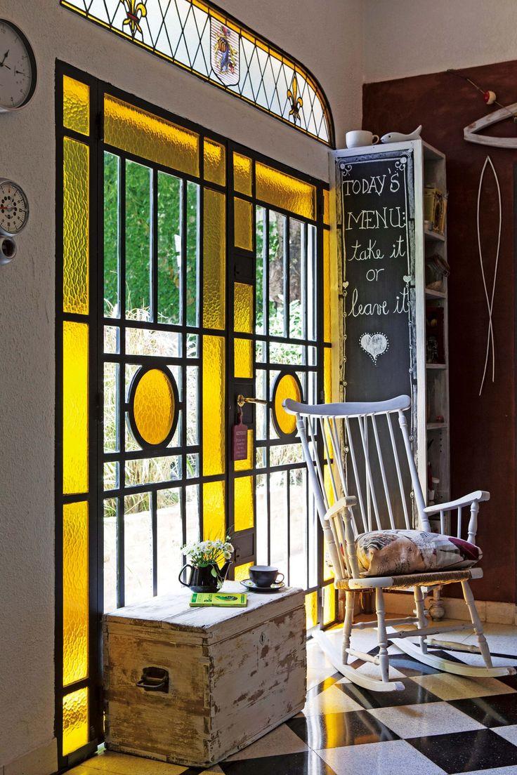 Cocina rústica con gran ventanal de vidrio repartido, piso en damero blanco y negro, y detalles en bordó.