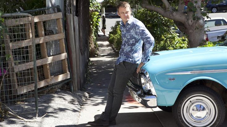 #Tom wears: #BenSherman blue faded floral print long sleeve cotton shirt; #Nudie grey cotton slim fit pants; #JuliusMarlowe brown/grey suede ankle boots.