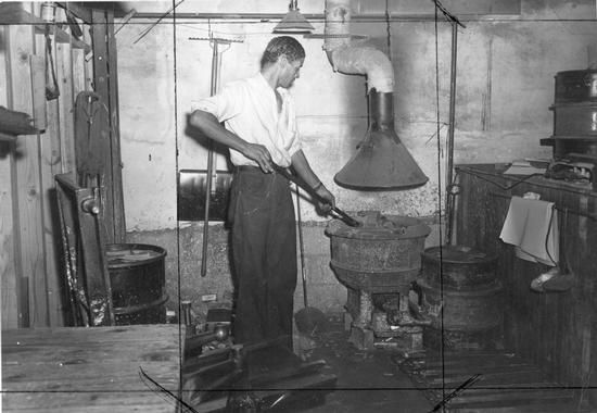In this undated photo a worker at the News Virginian works with the smelting furnace that was used for the printing process.