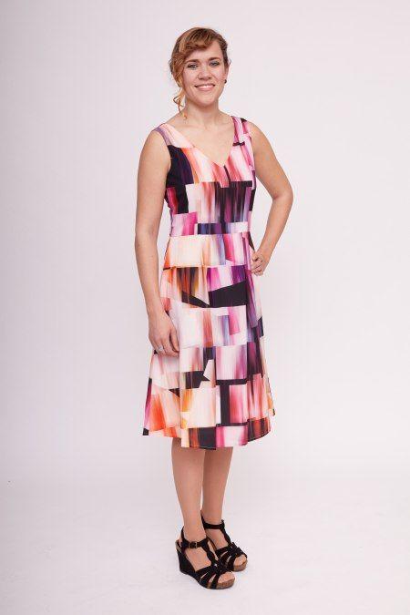 Dit mouwloze oranje jurkje heeft een grafische print met zwarte, paarse en gele tinten. Het jurkje heeft een v-hals aan de voor- en achterkant en heeft een hoge taille.