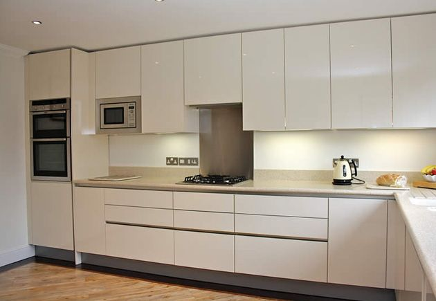 Handleless gloss acrylic cream kitchen.  Orderly base and wall units in the handless style create a neat and streamlined effect, whilst undercabinet lighting prevents the worktop area from becoming too dark. #creamkitchen #kitchen #LWKKitchens