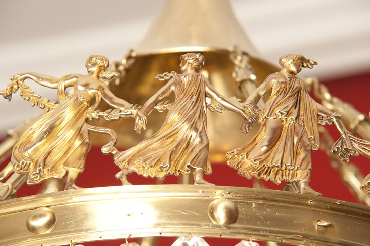 Detalle de lámpara de araña de bronce dorado y cristal de la Granja. Ostenta palmetas, rosetas y una orla circular con bacantes bailando, de bronce dorado. De época imperio. Siglo XIX. Salón rojo. Piso Entresuelo.