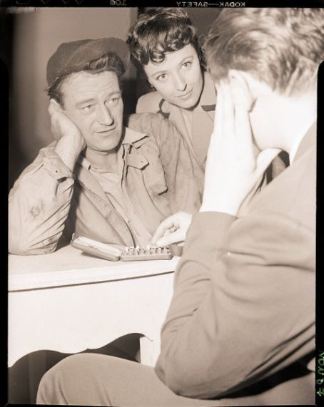 RKO-PICTURES - John Wayne plays chess between scenes - That's co-star Laraine Day at his shoulder.