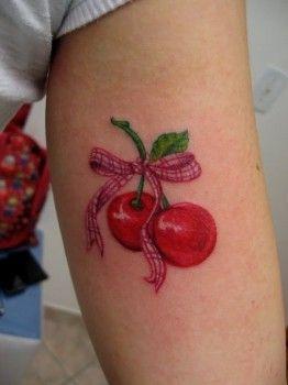 Dos preciosas cerezas de un color rojo brillante, que aparecen unidas por su tallo y por una bonita cinta rosa de cuadros. Un par de frutos muy bien defini