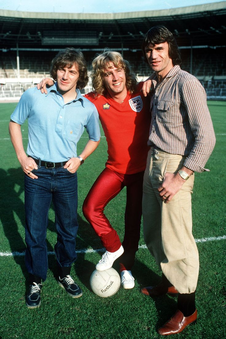 England footballers Steve Coppell (left) and Dave Watson (right) pose with Rick Parfitt, a keen football fan, circa 1980