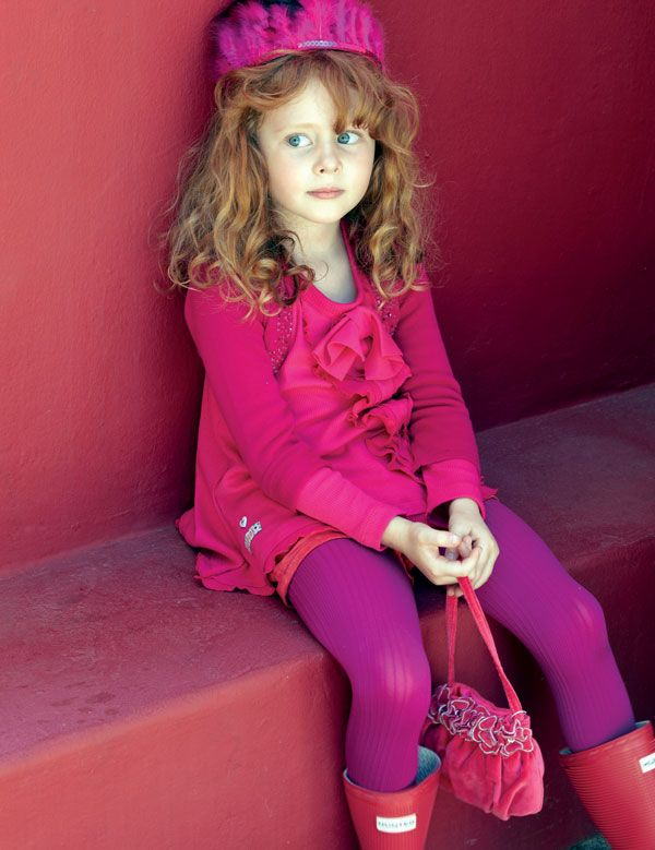 Kate (4) strikes a pose in a cerise tunic from Eco Punk, a bolero cardi with beaded detail from Accessorize and shorts from Jelli. Her boots are Hunters and the feather headpiece is also from Accessorize.