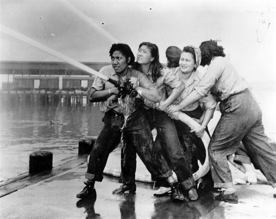 "Female firefighters fighting the fires at Pearl Harbor Naval Station. Volunteers AFTER the bombing.  ""A crew of women fire fighters, all crews having been chosen from personnel working in the immediate vicinity of the pumper stations. From left to right: Elizabeth Moku, Alice Cho, Katherine Lowe, and Hilda Van Gieson."""