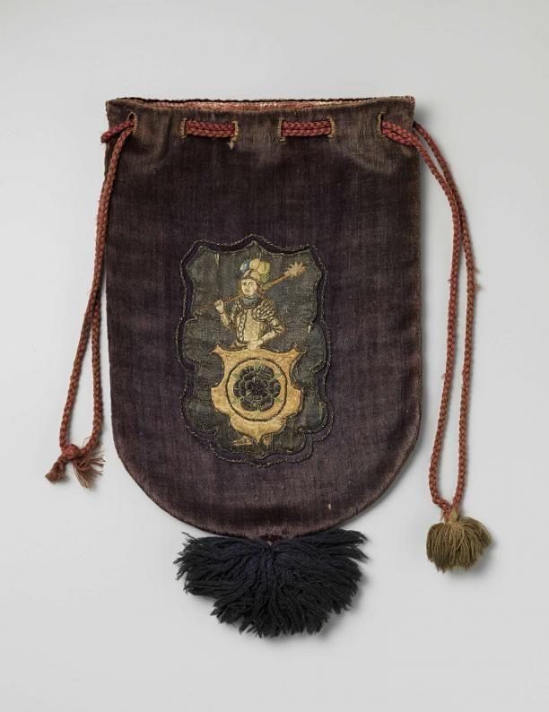 Buidel van paars fluweel, aan de voorzijde met zijde en zilverdraad het gemeentewapen van Schagen geappliqueerd, voorzien van wollen trekkoord en dito kwast | Modemuze