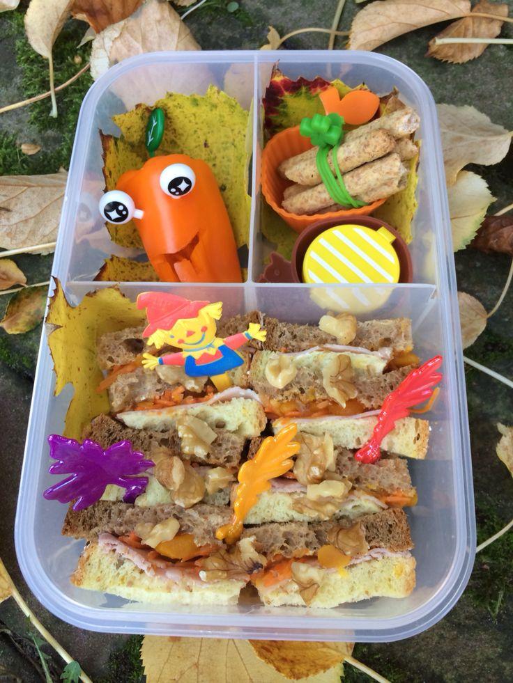 Vrolijke herfst lunchtrommel!  Sandwich van maisbrood en volkorenbrood, besmeerd met pompoenchutney, geraspte wortel en geitenkaas. Vervolgens snijdt je het brood in 8 stukjes en zet t rechtop in de lunchbox. Bestrooi met stukjes noot. #hellolunch