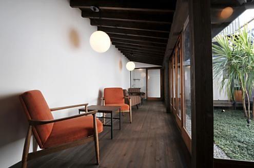 インナーテラスには、ひとり掛けのソファが並び、カフェのような雰囲気。廊下の先に101、102号室があります。(id:35941,リビング)