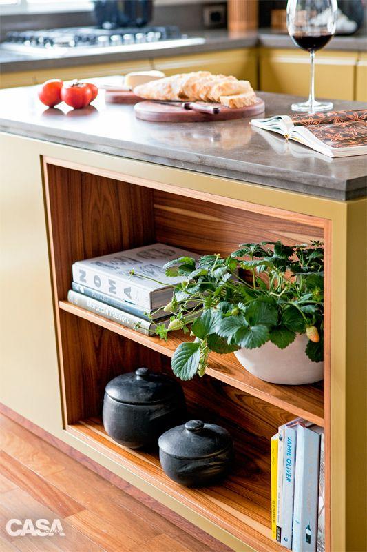 A ilha, equipada com forno embutido, tem nichos para livros voltados para a sala de jantar.