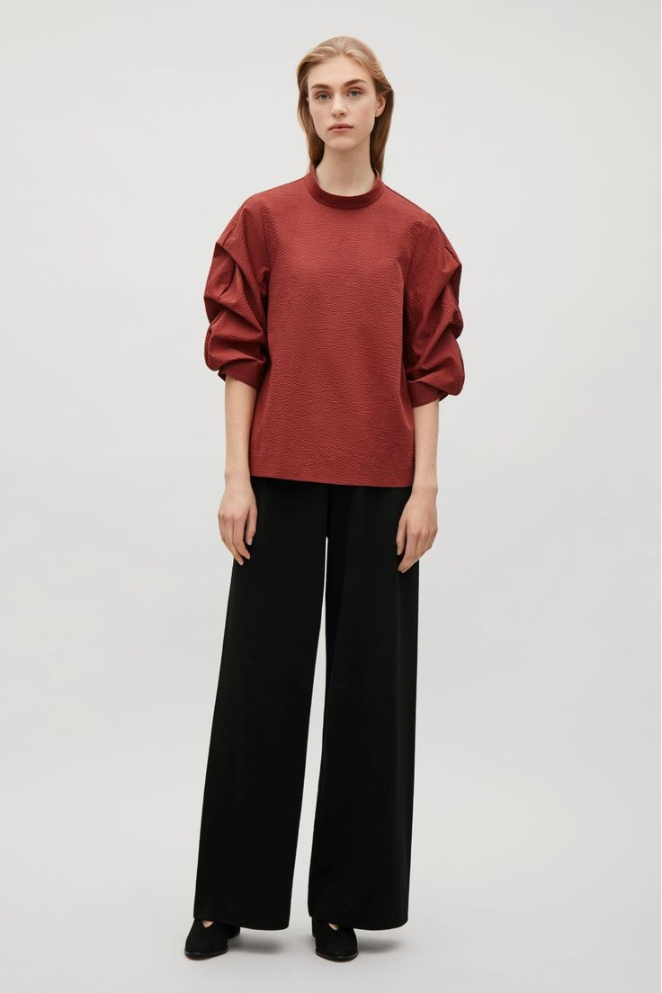 Designed with voluminous sleeves with draped pleats, this top is made from cotton with a puckered, tactile quality. A boxy fit, it has a neat, standing neckline, a hidden back zip and a simple, straight hemline.