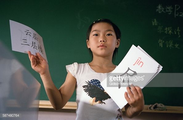 Young gymnast Zhao Chaoyue (8) holds up characters from the Chinese alphabet during a class at the Shishahai Elementary School. This is a normal state school, close to the Shishahai Sports School where she lives. She, and the other sports trainees, attend these lessons every morning and then do intensive gymnastic coaching in the afternoon.