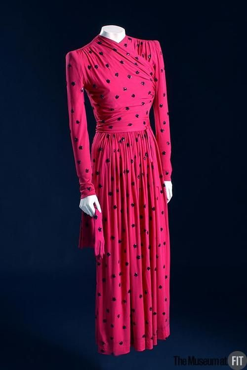 1940 dress by Elsa Schiaparelli in shocking pink polka dots with long sleeves. Via The Museum at FIT.